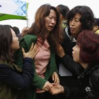 A family member cries Saturday after finding the name of a missing relative on a list of those who perished during last week's South Korean ferry sinking accident. | REUTERS