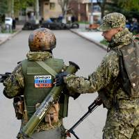 Armed men wearing military fatigues show off a sticker reading 'Donetsk don't listen to Kiev' during a pro-Russian rally Friday in the eastern Ukrainian city of Slovyansk. | AFP-JIJI