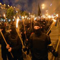 Unidentified Ukrainian ultranationalist activists march toward Kiev's Independence Square to commemorate 'Maidan heroes' Tuesday. | AFP-JIJI