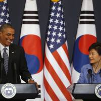 U.S. President Barack Obama listens to questions from reporters as South Korean President Park Geun-hye watches during a joint news conference after their meeting at the presidential Blue House in Seoul on Friday. | REUTERS