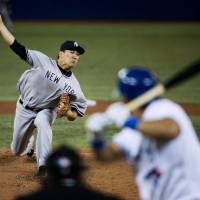 So it begins: Yankees starter Masahiro Tanaka pitches to the Blue Jays' Melky Cabrera in the first inning on Friday in Toronto. Tanaka earned the win in his MLB debut. | AP
