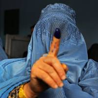 An Afghan woman shows her inked finger after voting at a polling station in the northwestern city of Herat on Saturday. | AFP-JIJI