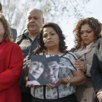 Families of victims of a General Motors safety defects in small cars hold photos of their loved ones as they gather on the lawn on Capitol Hill in Washington on April 1. | AP