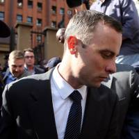 Oscar Pistorius leaves a Pretoria court Tuesday. Pistorius is charged with murder for the shooting death of his girlfriend, Reeva Steenkamp, on Valentines Day 2013. | AP