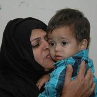 An unidentified family member comforts a 9-month-old boy at a lawyer's office in Lahore, Pakistan, on April 3. The Pakistani boy had been swept up in an attempted murder investigation that highlighted the country's dysfunctional criminal justice system where even children are not immune from questionable legal decisions. | AP