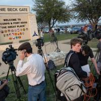 Members of the media wait outside an entrance to the Fort Hood military base for updates on a shooting that occurred inside on Wednesday. | AP