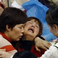 A family member of a missing passenger who was on the South Korean ferry Sewol cries as she waits for news from a rescue team at a gym in Jindo on Friday. | REUTERS