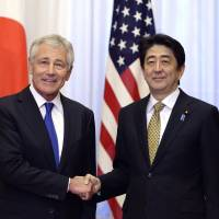 U.S. Secretary of Defense Chuck Hagel shakes hands with Prime Minister Shinzo Abe in Tokyo on Saturday. | POOL/AP