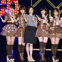 Mariko Tsukamoto (third from left), a 37-year-old mother who was picked from a pool of more than 5,000 applicants to join the all-female idol group AKB48, strikes a pose with some of its members at an event in Tokyo Thursday. | KYODO