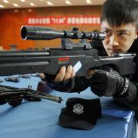 A SWAT team member checks a gun confiscated by Chinese police in Guiyang, Guizhou province, on March 6. Police in China have seized a huge cache of weapons including 15,000 guns and 120,000 knives from an illegal arms ring and detained 15 suspects, state media reported on April 14. | AFP-JIJI