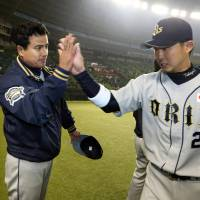 Triumphant finish: Buffaloes manager Hiroshi Moriwaki high-fives Takuya Hara after Orix's 2-1, 10th-inning win over the Seibu Lions on Friday at Seibu Dome. Hara had the game-winning hit. | KYODO