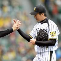 Job done: Hanshin manager Yutaka Wada (left) congratulates starting pitcher Atsushi Nomi during the Tigers' 9-0 win over the Giants on Saturday. | KYODO