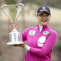 Weekend joy: Esther Lee holds the Studio Alice Ladies Open winner's trophy on Sunday in Miki, Hyogo Prefecture. | KYODO