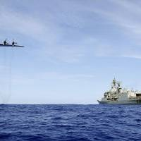 A Royal Australian Air Force AP-3C Orion from 92 Wing conducts a low-level flyby before dropping stores to HMAS Toowoomba during the search for the missing Malaysia Airways Flight MH370. | LSIS JAMES WHITTLE/AUSTRALIAN DEFENCE/AFP-JIJI