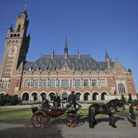 A horse-drawn carriage stands in front of the Peace Palace, the seat of the International Court of Justice in The Hague, on Aug. 28, 2013. The tiny Pacific nation of the Marshall Islands that was used for dozens of U.S. nuclear tests after World War II is taking on the United States and the world's eight other nuclear-armed nations with an unprecedented lawsuit demanding they meet their obligations toward disarmament and accusing them of 'flagrant violations' of international law. | AP
