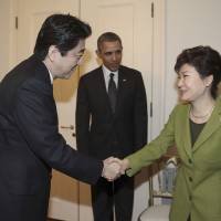 South Korean President Park Geun-hye shakes hands with Prime Minister Shinzo Abe on March 25 in The Hague, as U.S. President Barack Obama looks on before their trilateral meeting at the U.S. Ambassador's Residence in the Dutch city. | AP