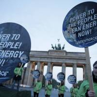 Members of environmental activist group Greenpeace pose with placards that read 'Power to the people! Clean energy now' in front of the Brandenburg Gate in Berlin on Sunday. The U.N. Intergovernmental Panel on Climate Change (IPCC) presented its third and final chapter of a mammoth overview on climate change the same day. | REUTERS