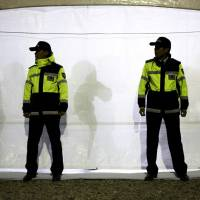 Police officers stand guard outside a tent acting as a temporary morgue for victims of the sunken South Korean ferry Sewol at the port of Jindo on Saturday. Some relatives of the more than 200 teenagers missing in the sunken vessel offered DNA swabs on Saturday to help identify the dead. | REUTERS