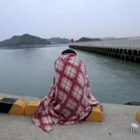 A relative waits in a port in Jindo, South Korea, for word of a missing loved one who was aboard a ferry that sank off the country's south coast Wednesday. The ship was carrying 459 people, mostly high school students on an overnight trip to a tourist island, and nearly 300 people remain missing. | AP