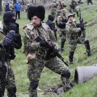 Armed pro-Russia protesters prepare to battle Ukrainian special forces on the outskirts the eastern city of Slovyansk on Sunday. | AFP-JIJI