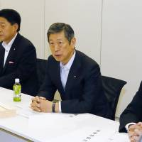 Liberal Democratic Party Vice President Masahiko Komura (second from right) speaks Tuesday during the second round of talks by the ruling coalition over revamping the nation's defense procedures. | KYODO