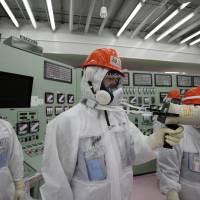 A Tokyo Electric Power employee measures radiation in the central operating control room for crippled reactors 1 and 2 at the Fukushima No. 1 nuclear plant on March 10. | REUTERS