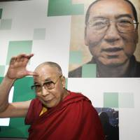 The Dalai Lama visits the Nobel Peace Center, where a picture of Chinese Nobel laureate Liu Xiaobo hangs as part of an exhibition, in Oslo on Friday. | AP