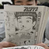 A man reads an 'Oishinbo' comic book last month in Tokyo. The series has come under fire for suggesting residents of Fukushima Prefecture are being sickened by radioactive fallout from the nuclear disaster. | KYODO