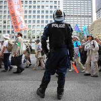 A police officer stands guard as hundreds of people march in Tokyo on Saturday vowing to protect the Constitution. | AP
