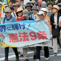 Participants in a Constitution Day rally march through central Tokyo on Saturday, urging Prime Minister Shinzo Abe to halt his attempt to alter the pacifist charter. | SATOKO KAWASAKI
