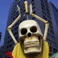A protester dressed as a skeleton holds up a mock World Cup trophy during a demonstration Thursday in Sao Paulo against the 2014 World Cup. | REUTERS