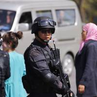 A Chinese SWAT unit guards the Urumqi railway station where three people died in a bomb and knife attack Wednesday. | REUTERS