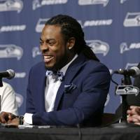 Stay a while longer: Seahawks cornerback Richard Sherman (center) smiles at a news conference on Wednesday flanked by head coach Pete Carroll (left) and GM John Schneider. | AP