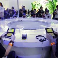 Attendees play games on the Nintendo 3DS at the Nintendo Wii U software showcase during last year's E3 game show in Los Angeles. Nintendo has said that, despite protest from some fans, it doesn't plan to allow same-sex romantic entanglements in its English version of the life-simulation game 'Tomodachi Life.' | AP