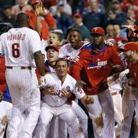Welcome wagon: Teammates wait to greet Philadelphia's Ryan Howard after his game-winning three-run homer against Colorado in the bottom of the ninth inning on Wednesday night. The Phillies downed the Rockies 6-3. | AP