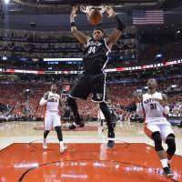 And that's the truth: Nets forward Paul Pierce dunks in front of a pair of Raptors during Game 7 of their first-round playoff series on Sunday in Toronto. Pierce blocked a shot on the final play to help Brooklyn hold on for a 104-103, series-clinching victory. | AP
