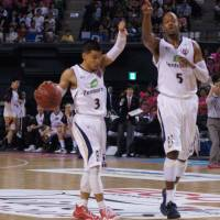 On the same page: Ryukyu guard Narito Namizato (left) and forward Anthony McHenry set up a play during Sunday's final against Akita. | TAKASHI SATO