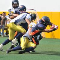 Ground attack: Nojima running back Takashi Miyako scores while being tackled by All Mitsubishi defensive back Kazumasa Matsuda in the first quarter on Sunday. | HIROSHI IKEZAWA