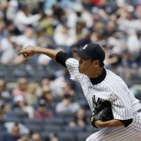Throwing darts: Yankee starter Hiroki Kuroda delivers a pitch during the first game of a twinbill against the Pirates on Sunday at Yankee Stadium. New York won the opener 4-3. | AP