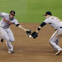 I got it: Baltimore shortstop J.J. Hardy and third baseman Ryan Flaherty converge on a ground ball from Houston's Alex Presley in the eighth inning on Thursday night. The Astros downed the Orioles 3-1. | AP