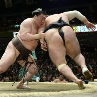 Strong start: Yokozuna Hakuho bulldozes Chiyootori in the raised ring on Sunday at the Summer Grand Sumo Tournament in Tokyo. | KYODO