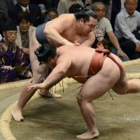 No sweat: Kakuryu (rear) takes down Yoshikaze at the Summer Grand Sumo Tournament at Ryogoku Kokugikan in Tokyo on Monday. | KYODO