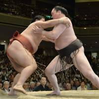 Man down: Hakuho (right) gets to grips with Yoshikaze at the Summer Grand Sumo Tournament on Sunday. | KYODO