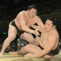 Master and disciple: Yokozuna Hakuho shoves Endo out of the ring at the Summer Grand Sumo Tournament on Monday. | KYODO