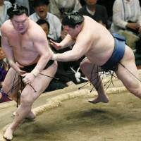 Get out of here: Goeido pushes yokozuna Hakuho out of the ring on Wednesday. | KYODO