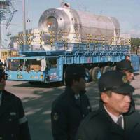 Riot police escort a canister containing 20 tons of nuclear waste from France in May 1997 as it is transported to a storage depot from a port in the northern village of Rokkasho, Aomori Prefecture. | AP