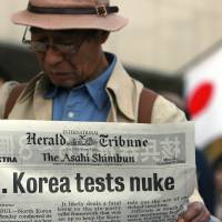 A pedestrian in Tokyo reads a special edition announcing North Korea's nuclear test in October 2006. Any nuclear test by Japan in future would likely cause a domestic and international uproar of a similar scale. | BLOOMBERG