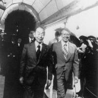 Prime Minister Takeo Fukuda walks beside U.S. President Jimmy Carter at the White House in March 1977. The U.S. voiced its concern at Tokyo's plans to build a reprocessing plant. | AP/KYODO