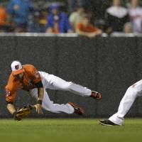 Slick play: Baltimore's David Lough (left) falls after catching a fly ball and colliding with teammate Manny Machado against Houston on Saturday. The Orioles edged the Astros 5-4. | AP