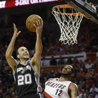 Smooth operator: Manu Ginobili goes up for a layup against Portland's LaMarcus Aldridge in Game 3 on Saturday. The Spurs ran past the Blazers 118-103 to take a 3-0 lead in the series. | AP
